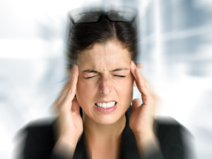 Businesswoman with intense stress and painful headache. Woman in job problems.